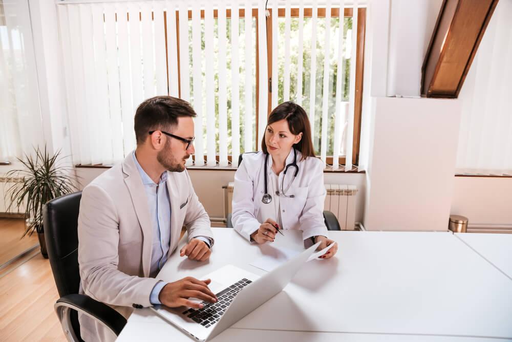 Dois médicos conversando em uma sala branca com cadeira o doutor homem está com um notebook analisando informações que vão ajudar na sua gestão hospitalar